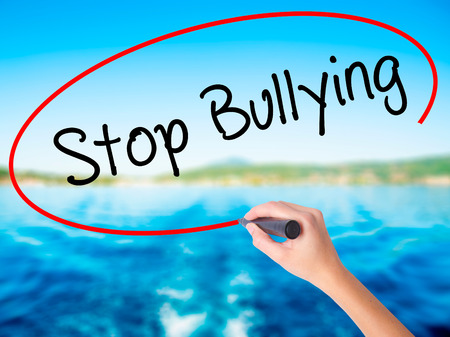 Woman Hand Writing Stop Bullying on blank transparent board with a marker isolated over water background. Business concept. Stock Photo