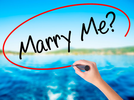 Woman Hand Writing Marry Me? with a marker over transparent board. Isolated on background. Business, technology, internet concept. Stock  Photo