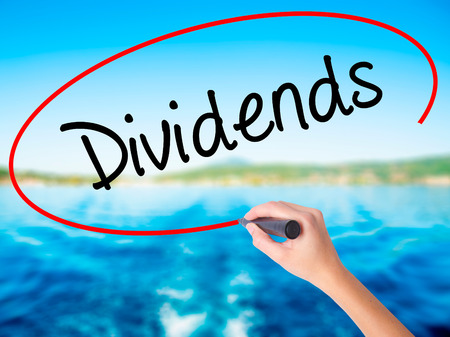 Woman Hand Writing Dividends on blank transparent board with a marker isolated over water background. Business concept. Stock Photo