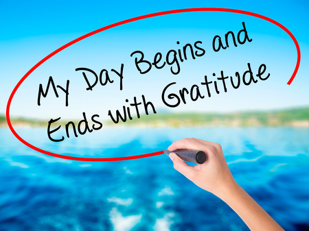 begins: Woman Hand Writing My Day Begins and Ends with Gratitude on blank transparent board with a marker isolated over water background. Business concept. Stock Photo