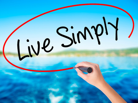 Woman Hand Writing Live Simply on blank transparent board with a marker isolated over water background. Business concept. Stock Photo Stock Photo