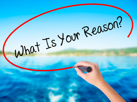 Woman Hand Writing What Is Your Reason? on blank transparent board with a marker isolated over water background. Business concept. Stock Photo
