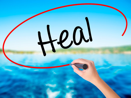 Woman Hand Writing  Heal  on blank transparent board with a marker isolated over water background. Business concept. Stock Photo