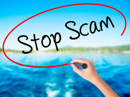 Woman Hand Writing Stop Scam on blank transparent board with a marker isolated over water background. Business concept. Stock Photo