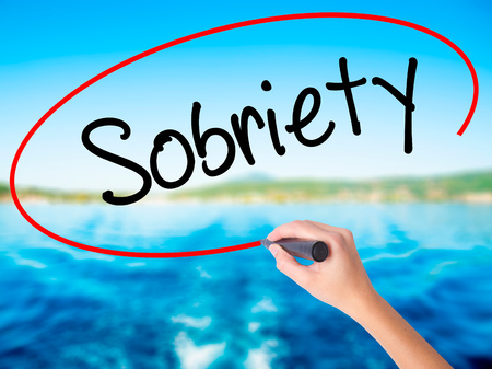 sobriety: Woman Hand Writing Sobriety on blank transparent board with a marker isolated over water background. Business concept. Stock Photo Stock Photo
