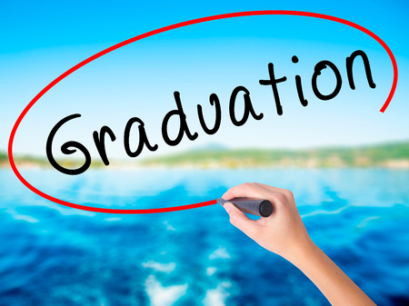 Woman Hand Writing Graduation on blank transparent board with a marker isolated over water background. Business concept. Stock Photo