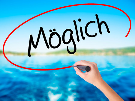 Woman Hand Writing Moglich (Possible in German) on blank transparent board with a marker isolated over water background. Business concept. Stock Photo