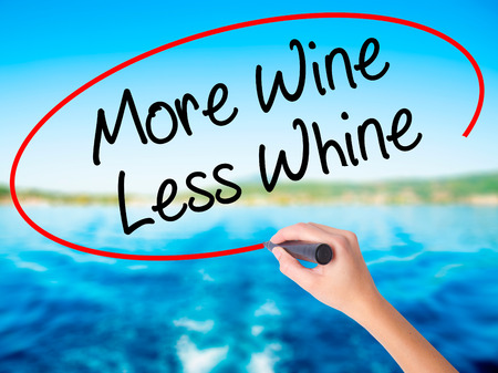 Woman Hand Writing More Wine Less Whine on blank transparent board with a marker isolated over water background. Business concept. Stock Photo Stock Photo