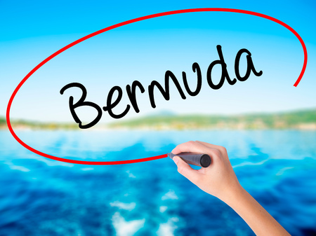 Woman Hand Writing Bermuda on blank transparent board with a marker isolated over water background. Business concept. Stock Photo