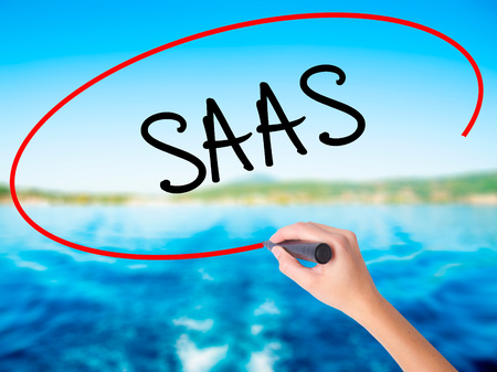 Woman Hand Writing SAAS on blank transparent board with a marker isolated over water background. Business concept. Stock Photo