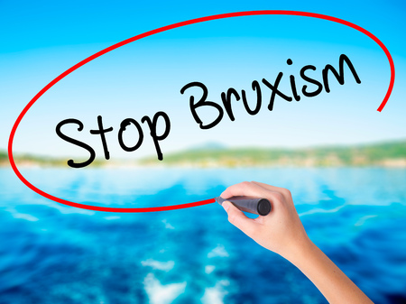 attrition: Woman Hand Writing Stop Bruxism on blank transparent board with a marker isolated over water background. Business concept. Stock Photo