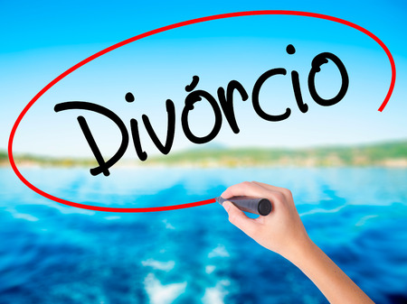 Woman Hand Writing Divorcio (Divorce in Portuguese) on blank transparent board with a marker isolated over water background. Business concept. Stock Photo