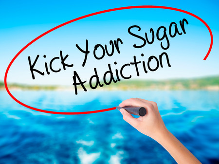 Woman Hand Writing Kick Your Sugar Addiction on blank transparent board with a marker isolated over water background. Business concept. Stock Photo