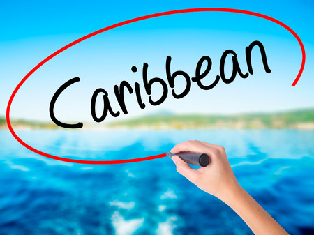 Woman Hand Writing Caribbean on blank transparent board with a marker isolated over water background. Business concept. Stock Photo Stock Photo