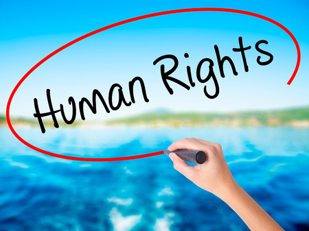 Woman Hand Writing Human Rights on blank transparent board with a marker isolated over water background. Business concept. Stock Photo