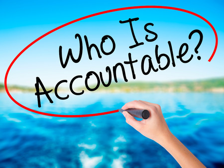 accountable: Woman Hand Writing Who Is Accountable? on blank transparent board with a marker isolated over water background. Business concept. Stock Photo