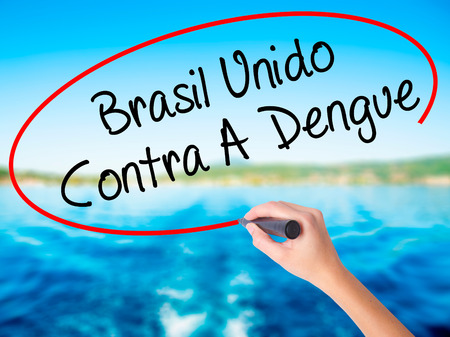 contra: Woman Hand Writing Brasil Unido  Contra A Dengue (Brazil against Dengue in Portuguese) on blank transparent board with a marker isolated over water background. Business concept. Stock Photo Stock Photo