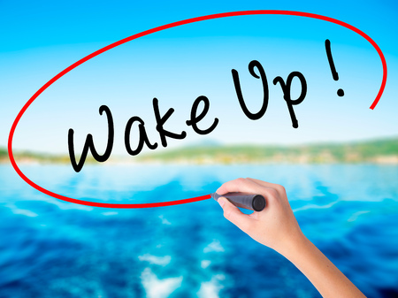 Woman Hand Writing Wake Up on blank transparent board with a marker isolated over water background. Business concept. Stock Photo