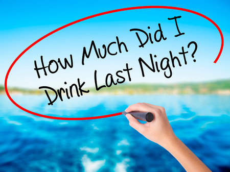 Woman Hand Writing How Much Did I Drink Last Night? on blank transparent board with a marker isolated over water background. Business concept. Stock Photo Stock Photo