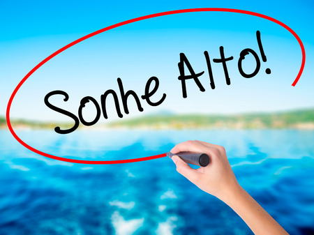 Woman Hand Writing Sonhe Alto! (Dream Big in Portuguese) on blank transparent board with a marker isolated over water background. Business concept. Stock Photo