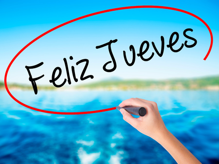 Woman Hand Writing Feliz Jueves (Happy Thursday In Spanish) on blank transparent board with a marker isolated over water background. Business concept. Stock Photo Stock Photo