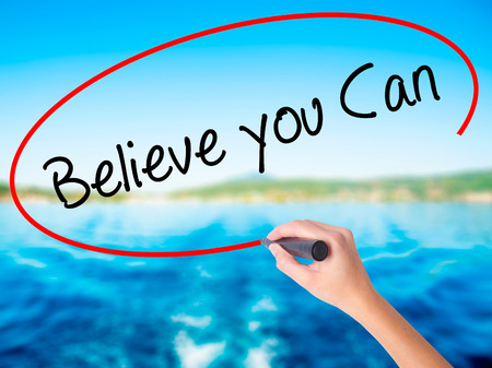 Woman Hand Writing Believe you Can on blank transparent board with a marker isolated over water background. Business concept. Stock Photo