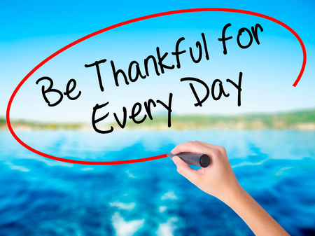 humility: Woman Hand Writing Be Thankful for Every Day   on blank transparent board with a marker isolated over water background. Business concept. Stock Photo
