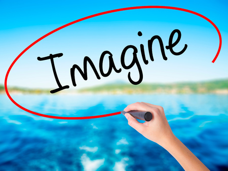 Woman Hand Writing Imagine on blank transparent board with a marker isolated over water background. Business concept. Stock Photo