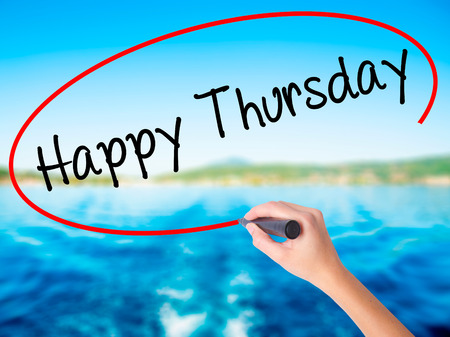 Woman Hand Writing Happy Thursday with a marker over transparent board. Isolated on background. Business, technology, internet concept. Stock  Photo