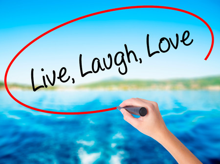 Woman Hand Writing Live Laugh Love on blank transparent board with a marker isolated over water background. Business concept. Stock Photo