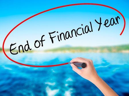 Woman Hand Writing End of Financial Year on blank transparent board with a marker isolated over water background. Business concept. Stock Photo