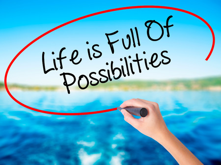 Woman Hand Writing Life is Full Of Possibilities on blank transparent board with a marker isolated over water background. Business concept. Stock Photo Stock Photo