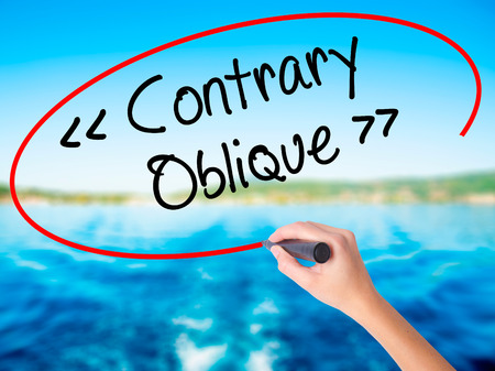 contrary: Woman Hand Writing Contrary - Oblique on blank transparent board with a marker isolated over water background. Business concept. Stock Photo Stock Photo