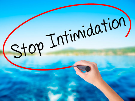 coercion: Woman Hand Writing Stop Intimidation on blank transparent board with a marker isolated over water background. Business concept. Stock Photo