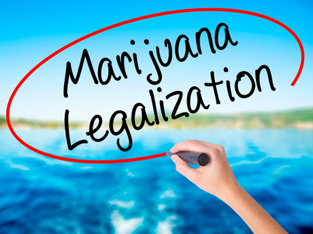 Woman Hand Writing Marijuana Legalization with a marker over transparent board. Isolated on white. Live, technology, internet concept. Stock Photo