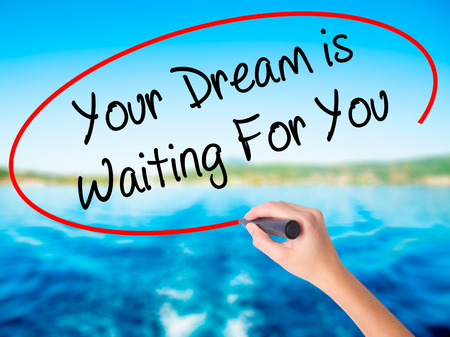 Woman Hand Writing Your Dream is Waiting For You on blank transparent board with a marker isolated over water background. Business concept. Stock Photo