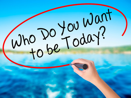 Woman Hand Writing Who Do You Want to be Today? on blank transparent board with a marker isolated over water background. Business concept. Stock Photo