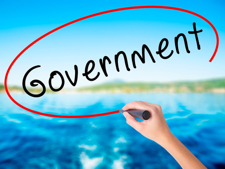 legislator: Woman Hand Writing Government on blank transparent board with a marker isolated over water background. Business concept. Stock Photo