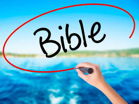 vangelo aperto: Woman Hand Writing Bible on blank transparent board with a marker isolated over water background. Business concept. Stock Photo