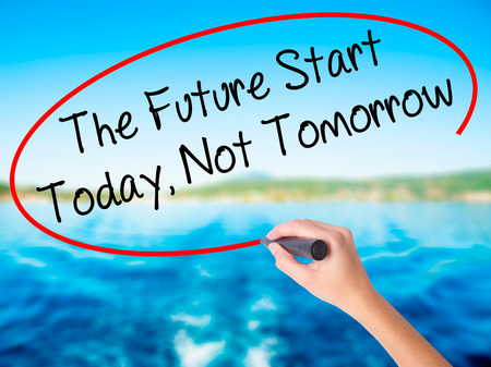 Woman Hand Writing The Future Start Today, Not Tomorrow on blank transparent board with a marker isolated over water background. Business concept. Stock Photo Stock Photo