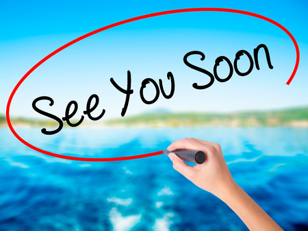 Woman Hand Writing See You Soon on blank transparent board with a marker isolated over water background. Business concept. Stock Photo