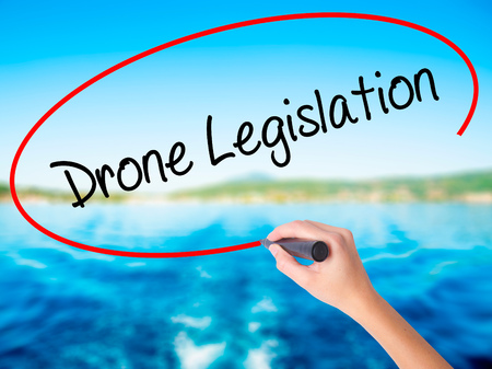Woman Hand Writing Drone Legislation on blank transparent board with a marker isolated over water background. Business concept. Stock Photo