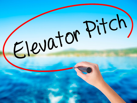 business pitch: Woman Hand Writing Elevator Pitch on blank transparent board with a marker isolated over water background. Business concept. Stock Photo