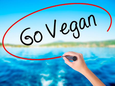Woman Hand Writing Go Vegan on blank transparent board with a marker isolated over water background. Business concept. Stock Photo