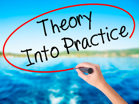 school strategy: Woman Hand Writing Theory Into Practice on blank transparent board with a marker isolated over water background. Business concept. Stock Photo