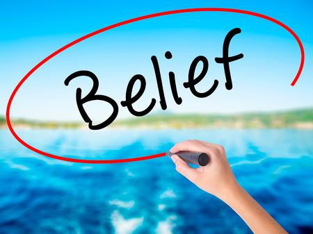 Woman Hand Writing Belief on blank transparent board with a marker isolated over water background. Business concept. Stock Photo