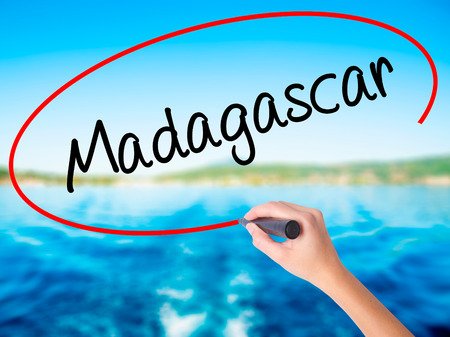 fort dauphin: Woman Hand Writing Madagascar on blank transparent board with a marker isolated over water background. Business concept. Stock Photo