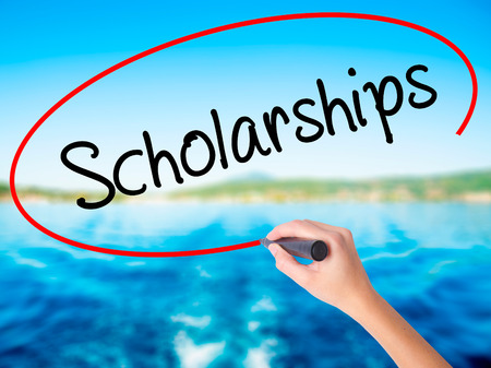 online degree: Woman Hand Writing Scholarships on blank transparent board with a marker isolated over water background. Business concept. Stock Photo