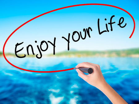 sucess: Woman Hand Writing Enjoy your Life on blank transparent board with a marker isolated over water background. Business concept. Stock Photo