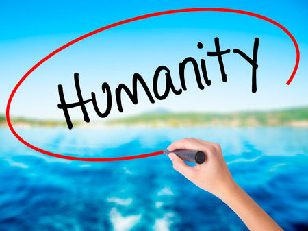 Woman Hand Writing Humanity  on blank transparent board with a marker isolated over water background. Business concept. Stock Photo